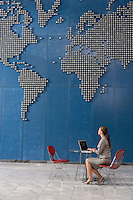 Business woman using laptop in office looking up at world map on wall