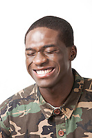 Happy young military soldier in camouflage clothing over white background
