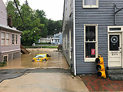 Ellicott City, Maryland - May 27, 2018: A taxi is engulfed by flood water in Historic Ellicott City.<br /> <br /> Historic Ellicott City Maryland was destroyed by floodwaters Sunday May 27, 2018 -- the same day of Kristen Rigney and Craig Cymbor's wedding at Main Street Ballroom in Ellicott City. Their wedding venue flooded minutes before their ceremony was scheduled and the entire wedding party fled to La Palapa, the Mexican food restaurant upstairs, where Craig and Kristen said their vows. Instead of eating, drinking and dancing, the wedding party, watched cars get swept away. <br /> CREDIT: Matt Roth