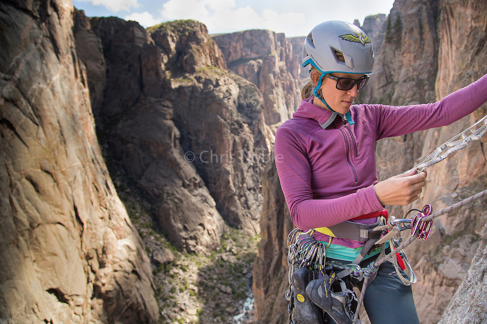 "Kate Rutherford prepares to rappel during an ascent of ""Tague Yer Time,"" 12b, South Rim, Black Canyon of the Gunnison, Colorado."
