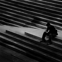A solitary male figure sitting on steps in an urban environment