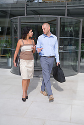 Two adults leaving their office building; talking,