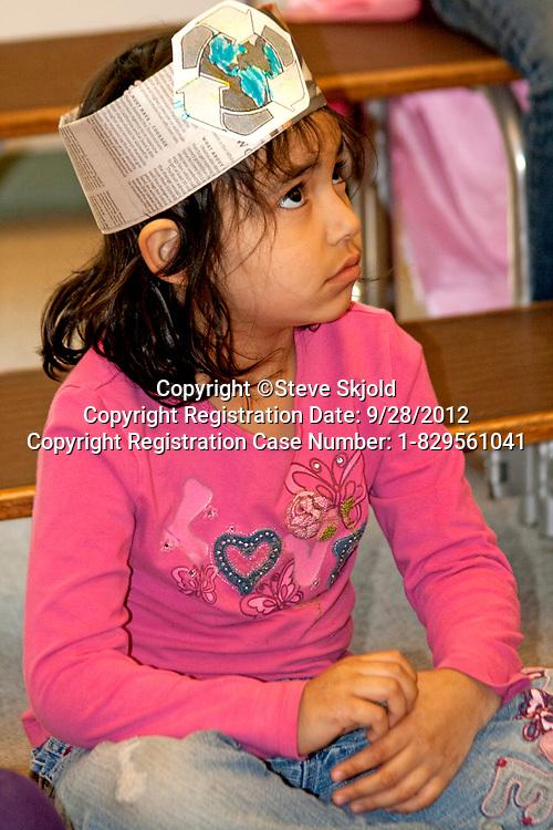 Asian American first grade female student part of a classroom recycling program. Horace Mann School St Paul Minnesota MN USA