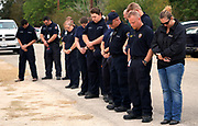 First responders who responded to the shooting at the First Baptist Church of Sutherland Springs, Texas, U.S. pray in the street at a Veteran's Day event in town November 11, 2017.  REUTERS/Rick Wilking