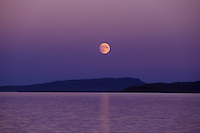 A full moon rises over Hornby and Denman Islands, two islands within the Strait of Gerorgia near the Comox Valley. The Comox Valley, Vancouver Island, British Columbia, Canada.