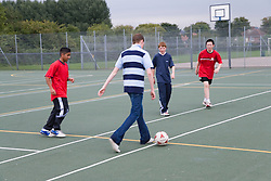 Group of teenage boys having a kick about with a football,