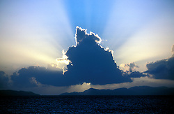 Sun rays backing a towering cloud. Horizontal.