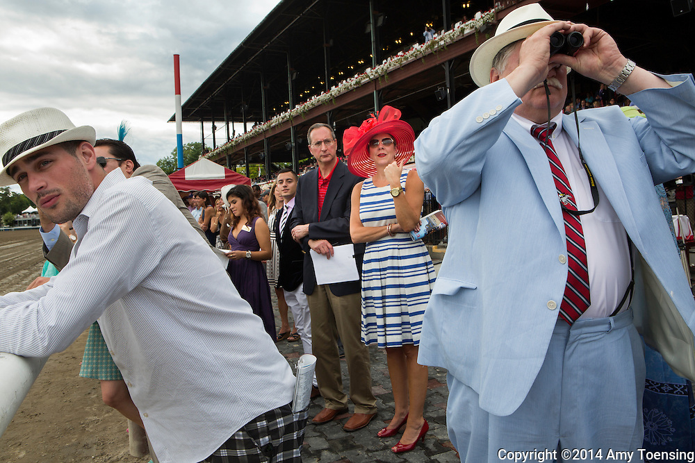 SARATOGA SPRINGS, NEW YORK - AUGUST 23, 2014: William Rohan (right) observes the game from the winners circle with his son, William P. Rohan (left) after winning a Lord &amp; Taylor fashion show on Travers Stakes day at the Saratoga Race Course in Saratoga Springs, NY. Photo by Amy Toensing _________________________________<br /> <br /> For stock or print inquires, please email us at studio@moyer-toensing.com.