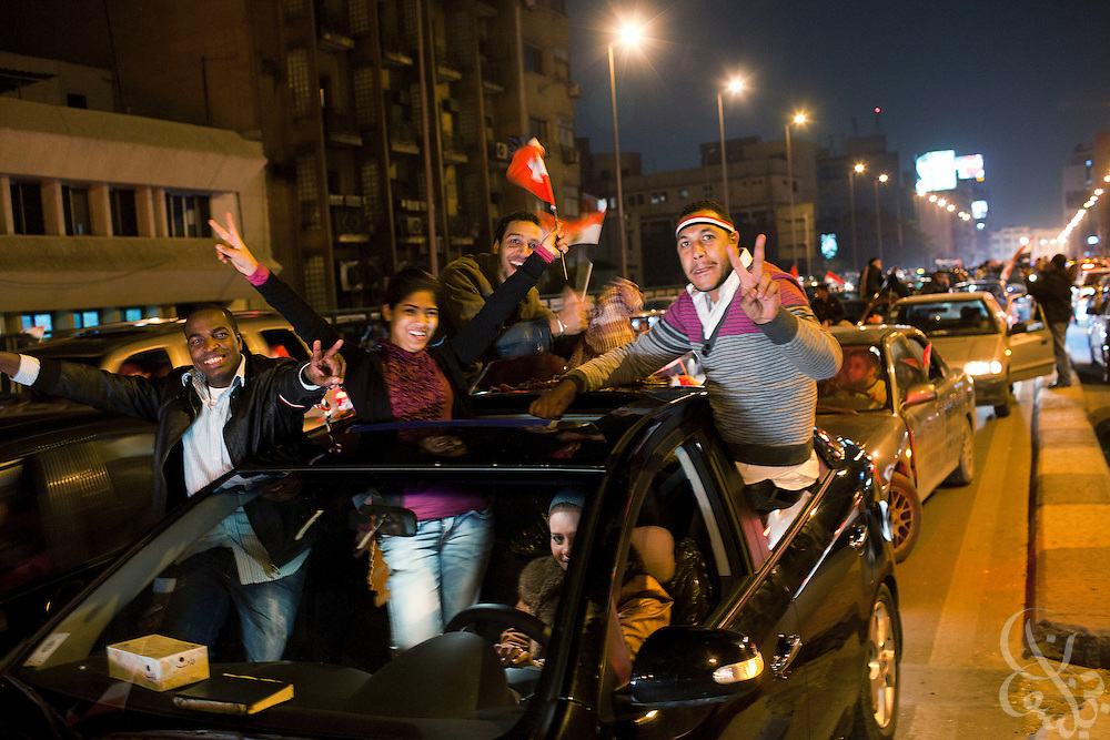 Egyptians wave flags and cheer atop cars through the 6th of October corridor in downtown Cairoafter hearing the news that Egyptian President Hosni Mubarak had stepped down February 11, 2011 following momentous marches on the public buildings across Cairo, Egypt. (Photo by Scott Nelson)