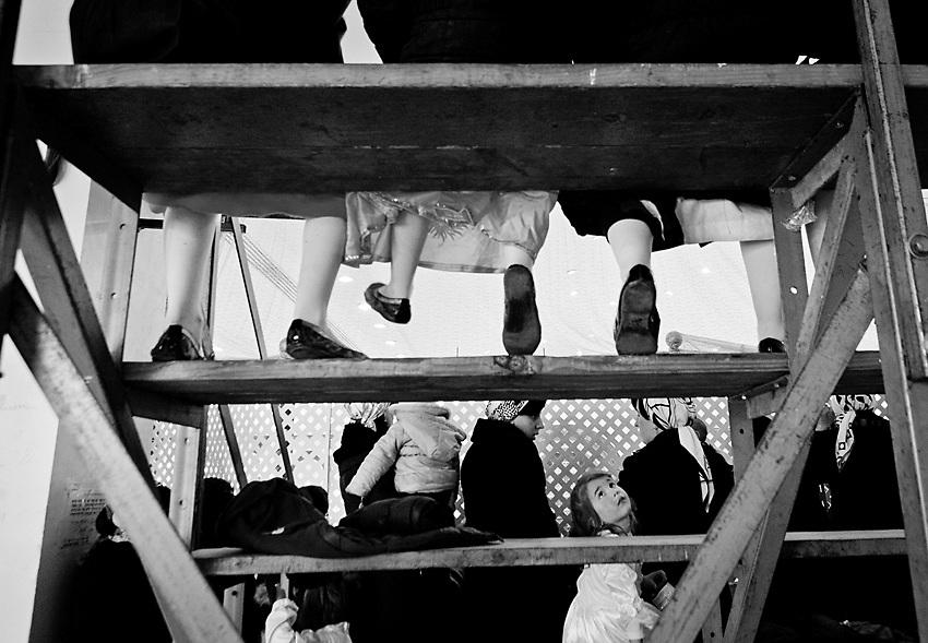 Bambine che giocano sulle scalinate provvisorie nella sezione delle donne durante il discorso Rebbe per Purim, il carnevale ebraico. Foto scattata il 16 Marzo, 2014.