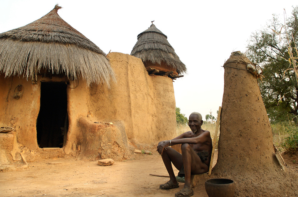 Natitingou December 2006 - An old man sits in front of his home in Natitingou, Benin.  The home is built in the Tata Somba architectural style. © Jean-Michel Clajot