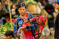 a young woman carrying her little kid and buying food in the local market of kalaw, myanmar