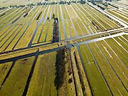 Nederland, Zuid-Holland, Gemeente Bergambacht, 20-02-2012; Krimpenerwaard met Polder Benedenkerk. Kenmerkend voor de inrichting van de polder zijn de regelmatig gevormde ontginningsblokken, zogeheten cope-ontginningen. Het water in het midden is de Ringsloot (Slingerkade), gegraven rond 1800 in het kader van de voorbereiding van het afgraven van veen. Door de tegenvallend kwaliteit van het veen is de veenderij echter gestaakt..Krimpenerwaard with Polde Benedenkerk. Characteristic for the 'design' of the polder are the regularly shaped reclamation blocks, known as cope reclamations. The water in the middle is the Ringsloot (ring ditch), excavated in 1800 in preparation for the excavation of peat. Because of the disappointing quality of the peat bog, however, the was discontinued..luchtfoto (toeslag), aerial photo (additional fee required);.copyright foto/photo Siebe Swart.