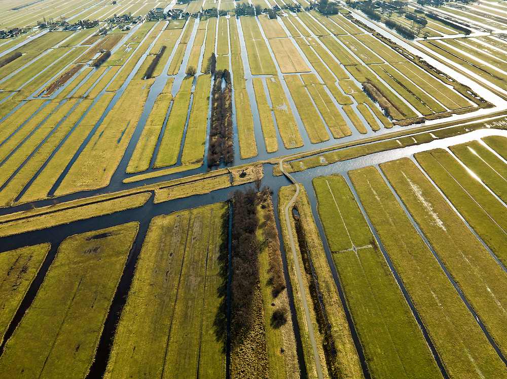 Nederland, Zuid-Holland, Gemeente Bergambacht, 20-02-2012; Krimpenerwaard met Polder Benedenkerk. Kenmerkend voor de inrichting van de polder zijn de regelmatig gevormde ontginningsblokken, zogeheten cope-ontginningen. Het water in het midden is de Ringsloot (Slingerkade), gegraven rond 1800 in het kader van de voorbereiding van het afgraven van veen. Door de tegenvallend kwaliteit van het veen is de veenderij echter gestaakt..Krimpenerwaard with Polde Benedenkerk. Characteristic for the 'design' of the polder are the regularly shaped reclamation blocks, known as cope reclamations. The water in the middle is the Ringsloot (ring ditch), excavated in 1800 in preparation for the excavation of peat. Because of the disappointing quality of the peat bog, however, the was discontinued..luchtfoto (toeslag), aerial photo (additional fee required);.copyright foto/photo Siebe Swart.