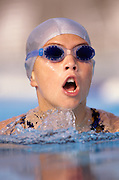 young girl during a swim meet race in a swimming pool with goggles and cap doing the breatst stroke