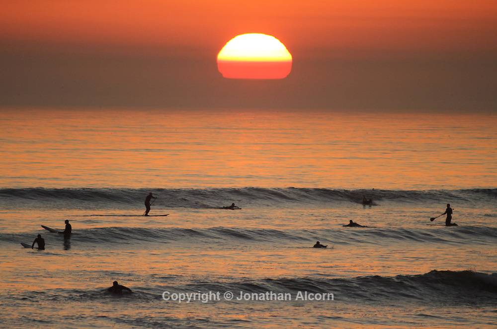 Suurfers and  paddle boarders enjoy the surf zone at sunset on a warm January winter day in Pacific Palisades