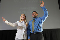 Man and woman waving from stage during business convention