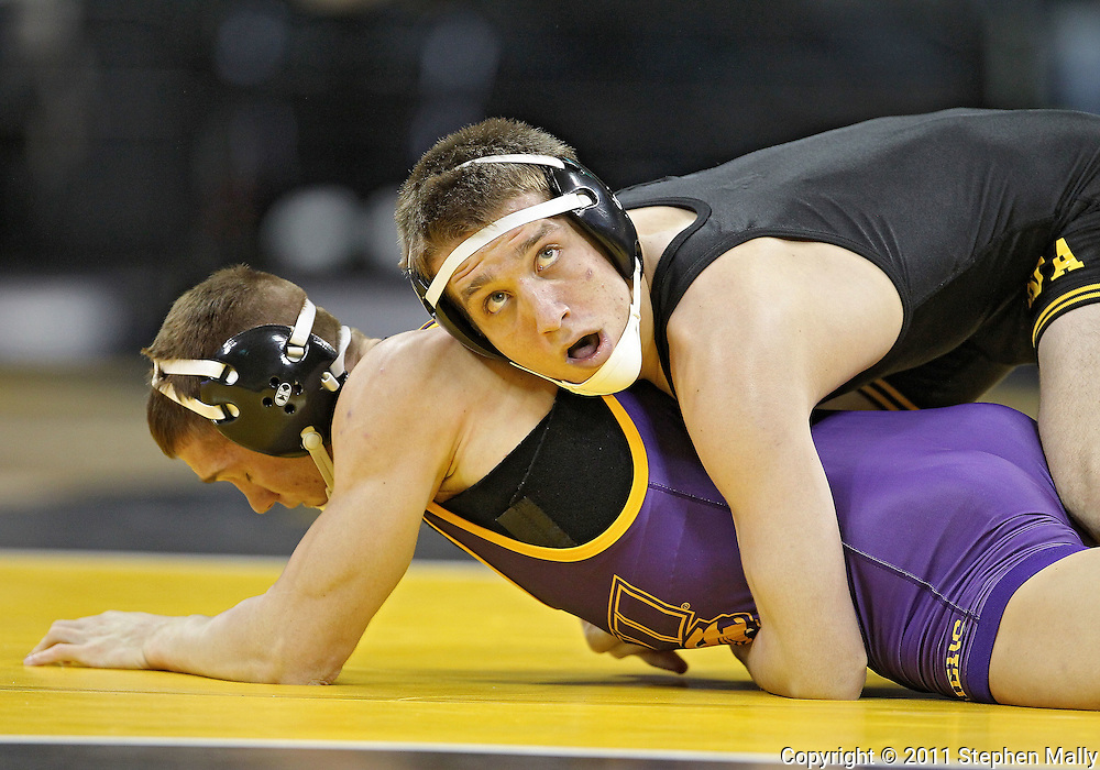 December 8, 2011: Iowa Hawkeyes Josh Dziewa glances up at the clock as he controls Northern Iowa Panthers Clay Welter in the 149 pound bout of the NCAA wrestling dual between the Northern Iowa Panthers and the Iowa Hawkeyes at Carver-Hawkeye Arena in Iowa CIty, Iowa on Thursday, December 8, 2011. Dziewa defeated Welter 14-6 and Iowa defeated Northern Iowa 38-4.