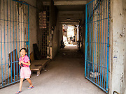 31 JANUARY 2013 - PHNOM PENH, CAMBODIA:  A girl leaves a Phnom Penh tenement building.    PHOTO BY JACK KURTZ