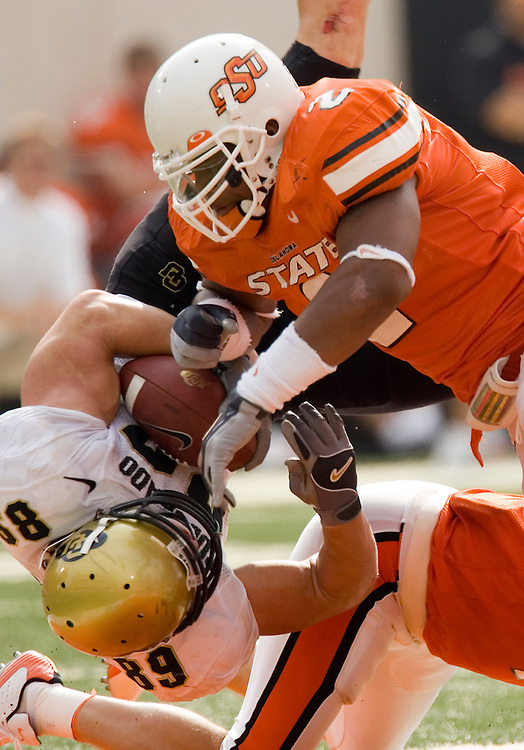 Colorado Buffaloes tight end Joe Klopfenstein gets upended after making a catch by Oklahoma State Cowboys defensive backs Stephen James and Chase Holland during a 34 to 0 win over the Oklahoma State Cowboys on October 1, 2005 at Boone Pickens Stadium in Stillwater, Oklahoma.