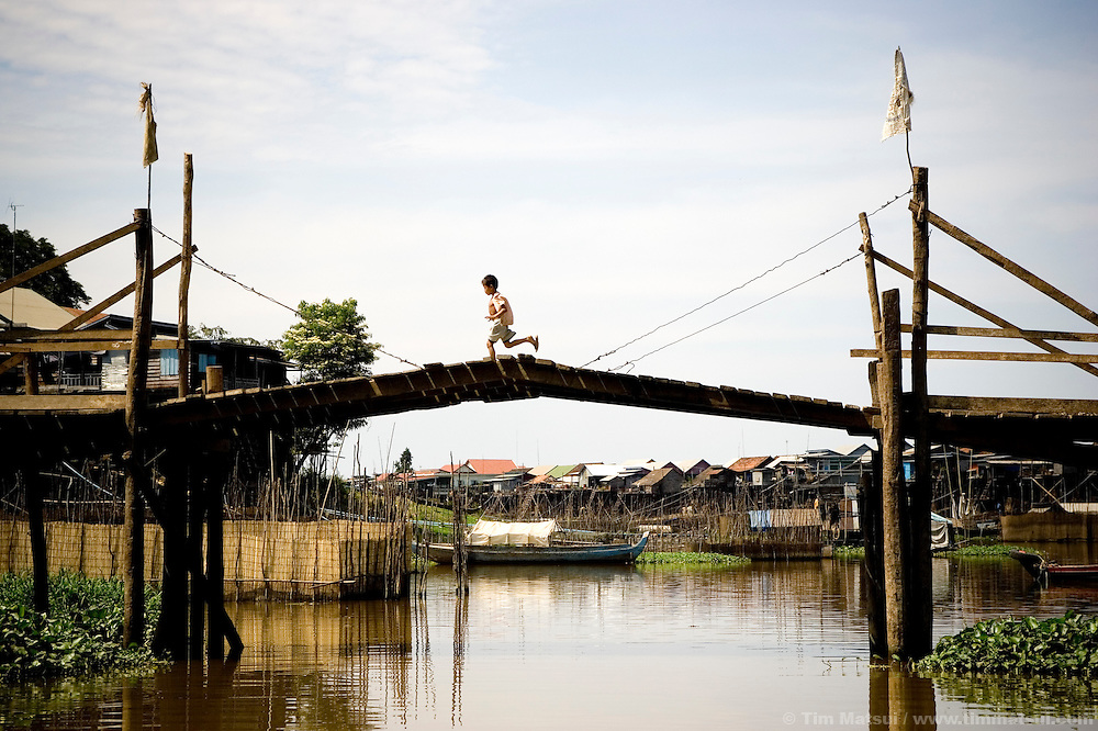 A young boy runs across a drawbridge in Moat Claws, a rural village near Siem Reap, Cambodia. The bridge and much of the village will be submerged beneath several meters of water when the Tonle Sap floods during the wet season.