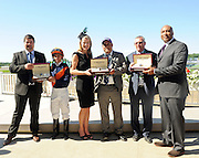 New York Yankees legend Bernie Williams, right, and Sebastien Zbinden, left, and Jennifer Judkins, both of Longines, present watches from the Longines Conquest Classic collection to jockey Javier Castellano, trainer Brian Lynch, second right, and owner representative Bob Feld, center, after their horse Coffee Clique won the $500,000 Longines Just a Game Stakes, Saturday, June 7, 2014, at Belmont Park in New York.  Longines, the Swiss watchmaker known for its elegant timepieces, is the Official Watch and Timekeeper of the 146th running of the Belmont Stakes. (Photo by Diane Bondareff/Invision for Longines/AP Images)