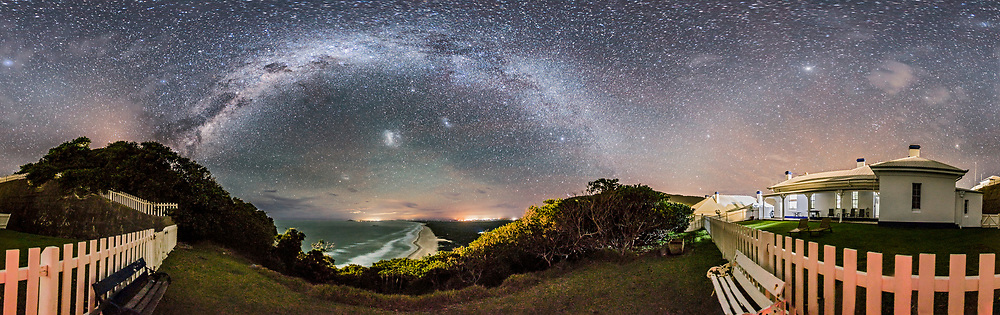 A 360&deg; panorama and from horizon to zenith of the southern sky and Milky Way from Smoky Cape and the grounds of the Lighthouse and Cottages. The Dark Emu in Crux and Centaurus is rising at left, while Canis Major and Sirius are setting right of center. The Magellanic Clouds are left of centre. The evening Zodiacal Light is visible arching up from the west at right, with Jupiter the bright object in the Zodiacal Band at right.<br /> <br /> The Lighthouse itself is just behind the trees on the hill at left and is ouf of sight though its beams are lighting the sky above the trees. Other sky colouration comes from light pollution and from airglow. <br /> <br /> I like the way the arch of the Milky Way mirrors the arch in the trees on the hillside sweeping down to the beach. I stayed for four nights in the cottage at right, and the dark window in the room at right was mine.<br /> <br /> The panorama is a stitch of 9 segments, each shot with the 15mm full-frame fish-eye lens in portrait orientation, and at f/2.8 with the Canon 6D at ISO 3200. All exposures 1 minute, untracked on a tripod. Stitched in PTGui using equirectangular projection.