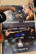 Johny Hendricks signs a stack of UFC 171 posters at his hotel in Dallas, Texas on March 11, 2014.
