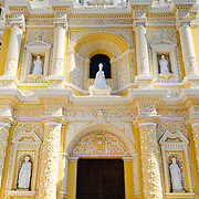 Front door of the distinctive  and ornate yellow and white exterior of the Iglesia y Convento de Nuestra Senora de la Merced in downtown Antigua, Guatemala.