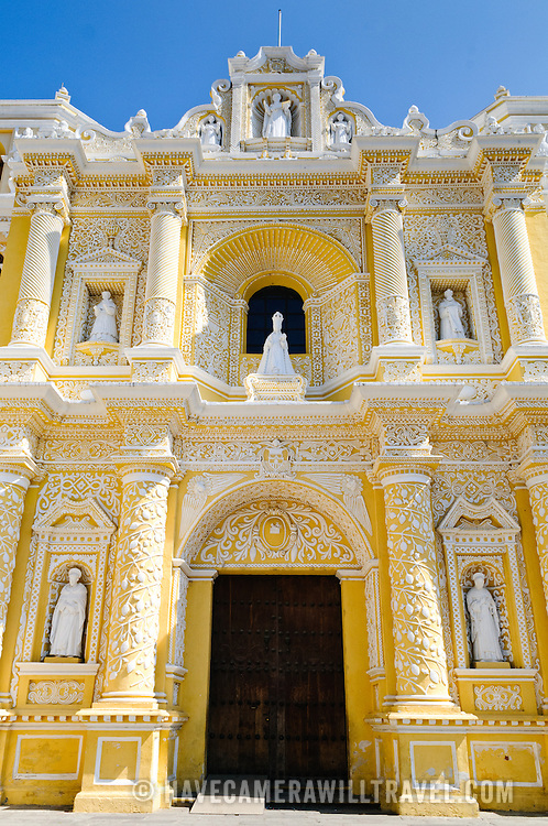 Front door of the distinctive  and ornate yellow and white exterior of the Iglesia y Convento de Nuestra Senora de la Merced in downtown Antigua, Guatemala.