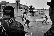 Anti-Qaddafi fighters from Benghazi engage on a firefight with snipers loyalists to Col. Muammar el-Qaddafi during a street fighting inside Qaddafi's hometown city of Sirte, Libya, on October 19, 2011. Photo by Mauricio Lima for The New York Times