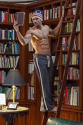 shirtless muscular man on a ladder in an at home library