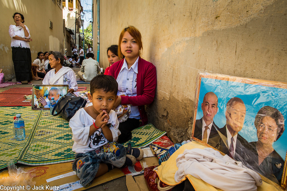 """04 FEBRUARY 2013 - PHNOM PENH, CAMBODIA:  Cambodians sit in an alley near the National Museum waiting for the cremation of King-Father Norodom Sihanouk to begin. Norodom Sihanouk (31 October 1922- 15 October 2012) was the King of Cambodia from 1941 to 1955 and again from 1993 to 2004. He was the effective ruler of Cambodia from 1953 to 1970. After his second abdication in 2004, he was given the honorific of """"The King-Father of Cambodia."""" Sihanouk died in Beijing, China, where he was receiving medical care, on Oct. 15, 2012.   PHOTO BY JACK KURTZ"""