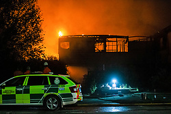 © Licensed to London News Pictures. 15/09/2020. Skelmersdale, UK. Fire crew attempt to bring large fire under control at former Co-op bank in Skelmersdale High Street. Orange glows and smoke seen for miles.  Photo credit: Kerry Elsworth/LNP