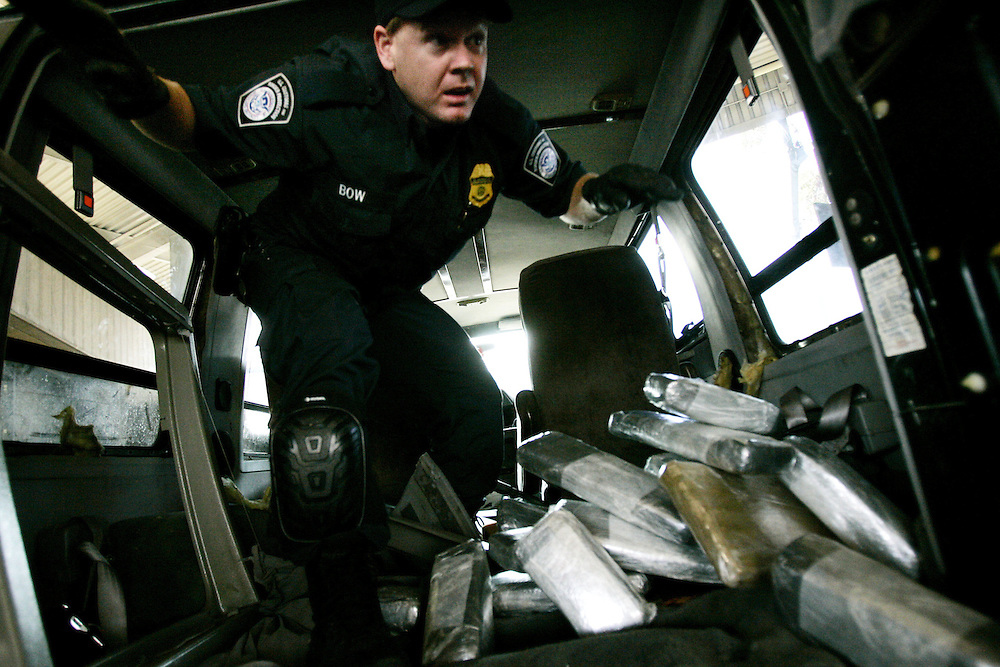Customs and Border Protection agent Ian Bow exits a van after pulling out bricks of Marijuana at the U.S. Port of Entry in San Ysidro, Calif.  The drugs were concealed throughout the van behind wall  paneling and in a chamber in the gas tank.