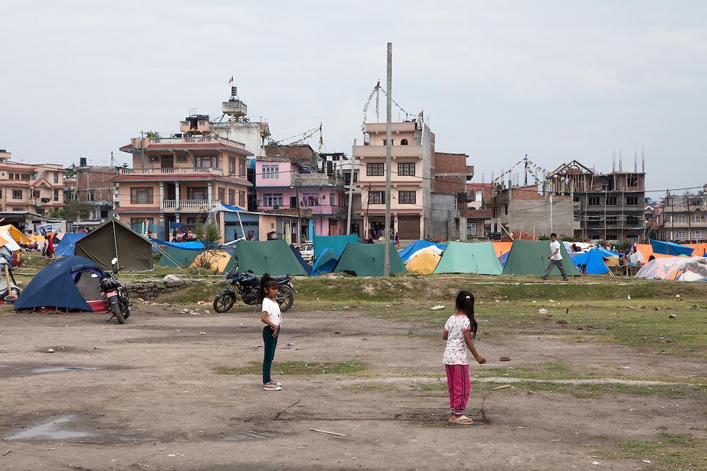 Meisjes spelen in een tentenkamp in de buitenwijk Boudhanath.