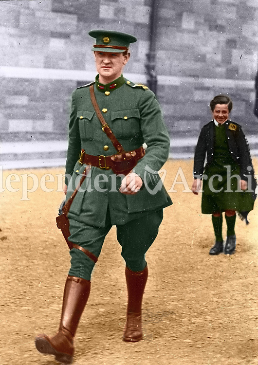 Michael Collins strides through Cathal Brugha Barracks, Dublin. A young civilian piper, Alphonsus Culloten, follows in tow. The shot was taken on Collins' return from a memorial service on the 7 August, 1922. Just over two weeks later, he was shot dead by anti-Treaty forces in Cork. This image has been digitally edited to add colour to its original black and white format. (Part of the Independent Newspapers Ireland/NLI Collection)