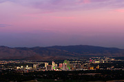 Reno, Nevada, downtown city skyline with casinos and mountains in the background at night