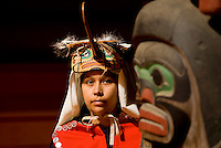 A young First Nations member of the Fort Rupert band displays her Hummingbird headdress and button blanket at the longhouse in Fort Rupert on Northern Vancouver Island.  British Columbia, Canada.