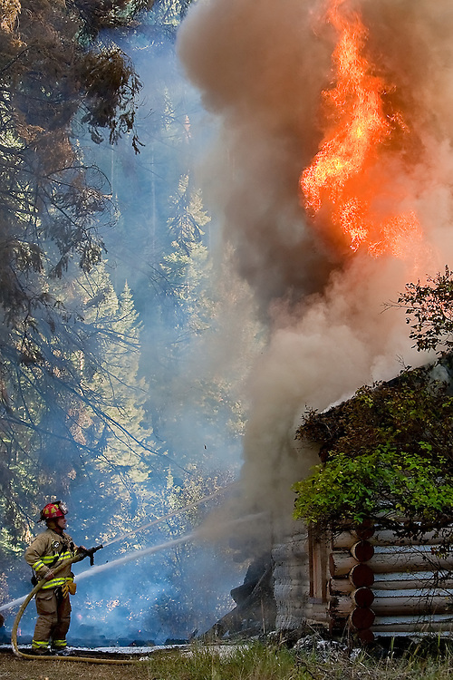 JEROME A. POLLOS/Press..A Kootenai County firefighter battles a cabin fire as a column of smoke and flames rise upward Wednesday at Wolf Lodge Creek Road and Marie Creek Road. The fire severed a powerline and required tanker trucks to shuttle water to fire crews.