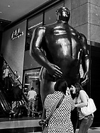 "Tourists enjoy themselves with ""Adam"", a sculpture by Fernando Botero  at the Time-Warner Center"