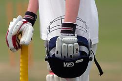 Boy playing cricket in whites holding his helmet & bat UK