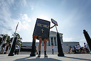 A protester dressed as a copy of the Bible joins groups demonstrating outside the U.S. Supreme Court in Washington. In one of the most closely watched cases of the year, brought by Hobby Lobby, the nine-member court will weigh whether for-profit corporations may raise religious objections to a mandate in President Barack Obama's signature 2010 healthcare law that their insurance cover contraceptives.