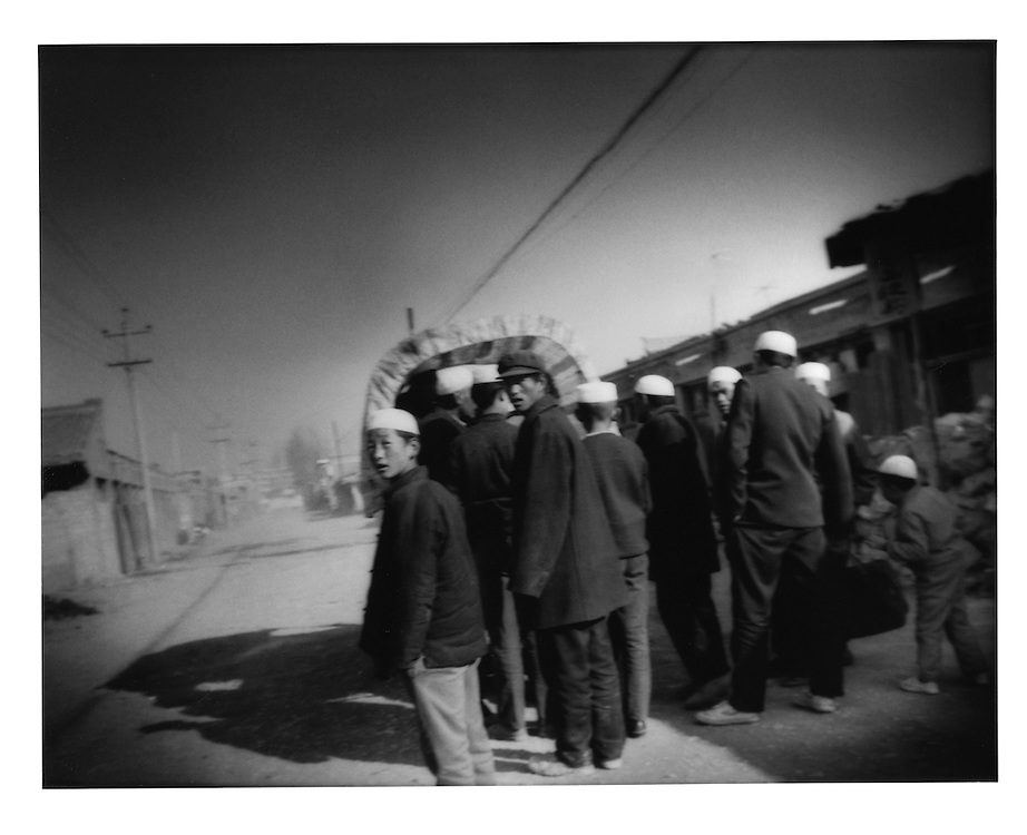 Hui Muslim men and boys prepare to climb into back of truck to carry them to former Silk Road town of Linxia, Gansu, China.