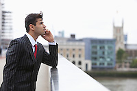 Side view of serious Indian businessman on call outdoors