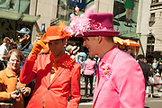Two men dressed as dandies, one in orange, the other in magenta.