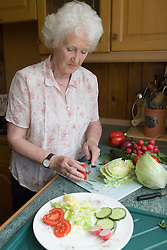 Woman preparing a salad in her kitchen,