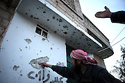 Villagers point to bullet wholes in the walls of a house in Kureen. On 22. February the syrian army attacked the village of Kureen, Province of Idlib, Syria. Kureen was among the first villages in the northwest of Syria controlled by the opposition. Some villagers and members of the defence units escaped to surrounding olive orchards, when the attack begun in the early morning. A majority of the inhabitants didn´t manage to escape. The heavy shelling lasts 7 houres. Soldiers searched all houses, burnt some of them down, loote shops, stole cars and furniture. About 60 motorcycles were burnt down. Tanks demolished several houses. 6 men were executed. One woman died as a result of an heart attack.