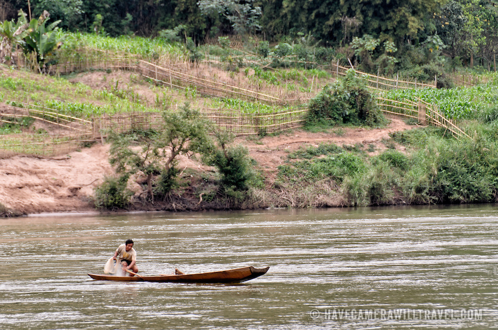 A man using a net to fish from his wooden canoe on the Nam Ou (River Ou) in Nong Khiaw in northern Laos.