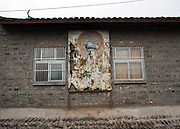 The remains of a communist- style revolutionary poster hang on a wall in  historical village of Lizhuang in Sichuan, China. The village was first established 1,800 tears ago, although the present town was built during the Ming Dynasty. Lizhuang contains numerous preserved old streets and historic structures, including palaces and temples in classical styles, traditional courtyards, and narrow streets paved with blue stones.